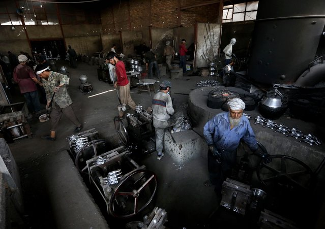 Afghan labors work on cooking pots made out of aluminum at a factory, on the outskirts of Kabul, Afghanistan, Tuesday, August 4, 2015. (Photo by Rahmat Gul/AP Photo)