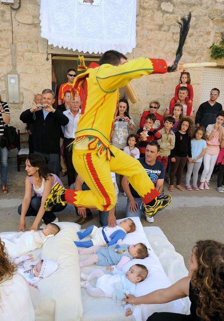 A man representing the devil leaps over babies during the festival of El Colacho in Castrillo de Murcia near Burgos, Spain