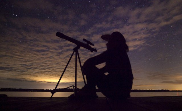 A stargazer waits for light clouds to clear to watch the Perseid meteor shower to begin near Bobcaygeon, Ontario, August 12, 2015. (Photo by Fred Thornhill/Reuters)