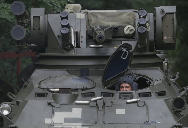 An employee of the Kiev armored plant sits inside a new Ukrainian armored personnel carrier BTR-3E1U during a test outside Kiev, Ukraine, August 14, 2015. (Photo by Valentyn Ogirenko/Reuters)
