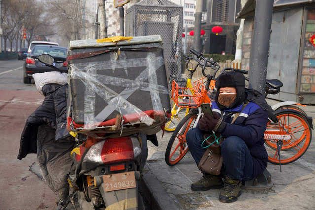 A deliver man uses his phone while waiting on a street of Beijing, China Tuesday, February 11, 2020. China's daily death toll from a new virus topped 100 for the first time and pushed the total past 1,000 dead, authorities said Tuesday after leader Xi Jinping visited a health center to rally public morale amid little sign the contagion is abating. (Photo by Ng Han Guan/AP Photo)