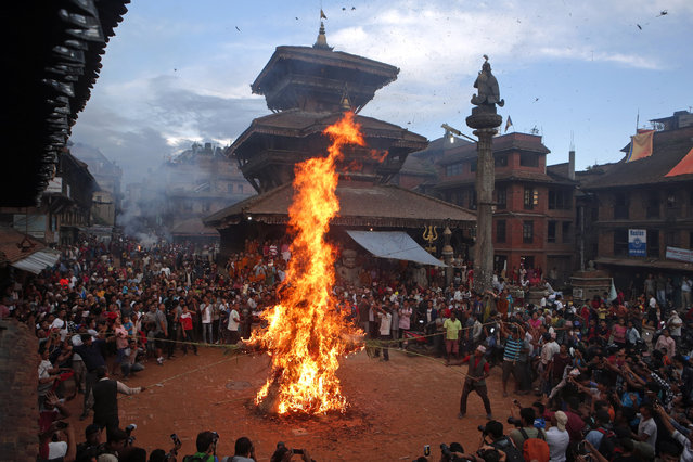 Nepalese people burn an effigy of demon Ghantakarna to represent demolition of evil during the Ghantakarna festival in Bhaktapur, Nepal, Friday, July 21, 2017. The festival is believed to ward off evil spirits, and bring peace and prosperity. (Photo by Niranjan Shrestha/AP Photo)