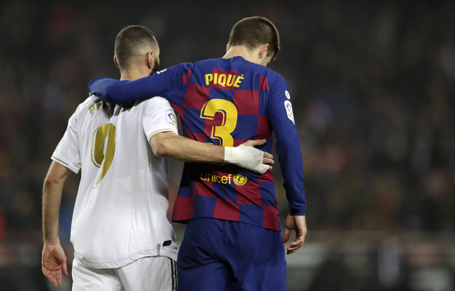 """Real Madrid's Karim Benzema, left, and Barcelona's Gerard Pique walks together on the pitch during a Spanish La Liga soccer match between Barcelona and Real Madrid at Camp Nou stadium in Barcelona, Spain, Wednesday, December 18, 2019. Thousands of Catalan separatists are planning to protest around and inside Barcelona's Camp Nou Stadium during Wednesday's """"Clasico"""". (Photo by Bernat Armangue/AP Photo)"""