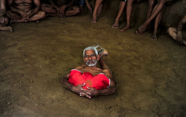 Elderly Indian wrestler, Ram Gopal performs during a bout of traditional wrestling organized at the historical Loknath Vyayamsala (Fitness Center) on the occasion of Nag Panchami, in Allahabad on August 1, 2014. The Hindu festival of Nag Panchami is observed during the monsoon with prayers and tributes to snakes. (Photo by Sanjay Kanojia/AFP Photo)