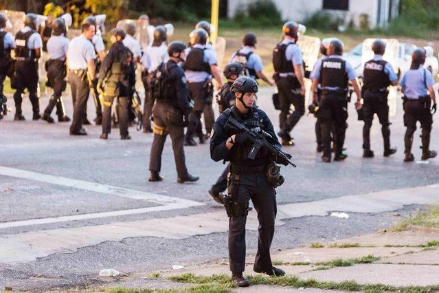 Police line up to block the street as protesters gathered after a shooting incident in St. Louis, Missouri August 19, 2015. (Photo by Kenny Bahr/Reuters)