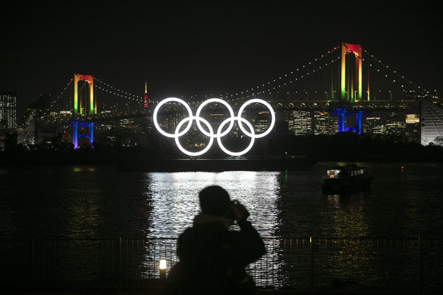 A photographer takes pictures of the illuminated Olympic rings in front of the Rainbow Bridge Friday, January 24, 2020, in the Odaiba district of Tokyo. Tokyo put on a flashy fireworks display on Friday to mark the 6-months-to-go milestone for this summer's Olympics. (Photo by Jae C. Hong/AP Photo)