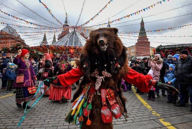 A performer wearing a mask dances and entertains the public during the Shrovetide Spring festival, near the Kremlin, in Moscow on February 24, 2020. Shrovetide or Maslenitsa is an ancient farewell ceremony to winter, traditionally celebrated in Belarus, Russia and Ukraine and involves the burning of a large effigy. (Photo by Yuri Kadobnov/AFP Photo)