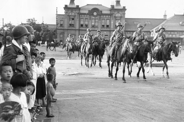 A South Korean cavalry regiment make their way to Taegu Station, on their way to the front line of the Korean War, 16th September 1950.  (Photo by Bert Hardy)