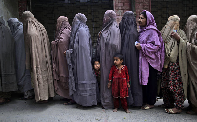 Pakistani women line up to enter a polling station and cast their ballots, on the outskirts of Islamabad, Pakistan, Saturday, May 11, 2013. (Photo by Muhammed Muheisen/AP Photo)