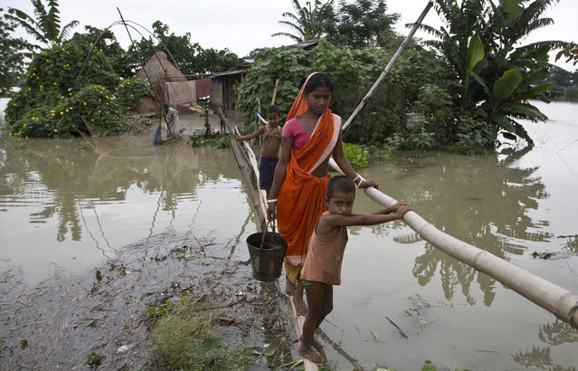 Locals affected by monsoon rains walk through a makeshift bridge in Mayong village, about 55 kilometers (34 miles) east of Gauhati, India, Sunday, August 23, 2015. The flooding in India's northeastern Assam state is the worst in the past three years, affecting nearly 600,000 people in 19 of the state's 27 districts, officials said. (Photo by Anupam Nath/AP Photo)