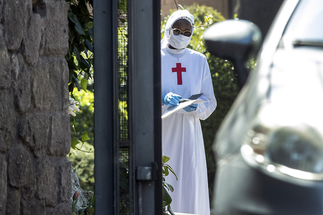 A nun wearing a mask and gloves stands at the Istituto Figlie di San Camillo (Institute of Daughters of St. Camillo) in Grottaferrata, near Rome, Friday, March 20, 2020. Outbreaks of the coronavirus have stricken two convents in the Rome area. Rome daily Il Messaggero quoted the Lazio region's health commissioner on Friday as saying 59 nuns at the Institute of Daughters of St. Camillo in the hill town of Grottaferrata have tested positive for COVID-19. (Photo by Roberto Monaldo/LaPresse via AP Photo)