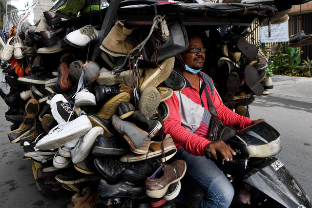 A man rides a motorcart loaded with secondhand shoes for sale along a street in Phnom Penh, Cambodia on March 24, 2020. (Photo by Tang Chhin Sothy/AFP Photo)