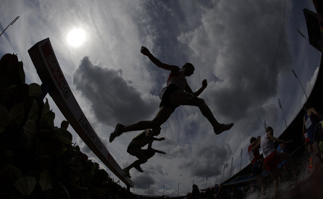 In this photo taken with a fisheye lens athletes clear an obstacle in the men's 3000m steeplechase qualification during the European Athletics Championships in Zurich, Switzerland, Tuesday, August 12, 2014. (Photo by Matt Dunham/AP Photo)