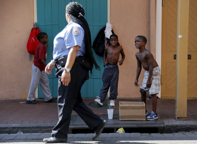 A New Orleans Police Department officer passes by boys tap dancing in the French Quarter one day before the ten year anniversary of Hurricane Katrina in New Orleans, Louisiana, August 28, 2015. (Photo by Jonathan Bachman/Reuters)