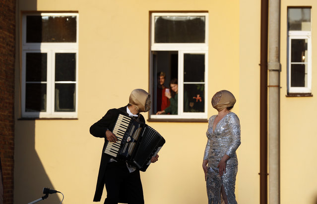 Street musicians entertain residents, as people stay in their houses to counter the spread of coronavirus, in Prague, Czech Republic, Tuesday, April 7, 2020. The Czech Republic's government has incorporated dramatic restrictive measures to try and stem the spread of the new coronavirus called COVID-19. (Photo by Petr David Josek/AP Photo)
