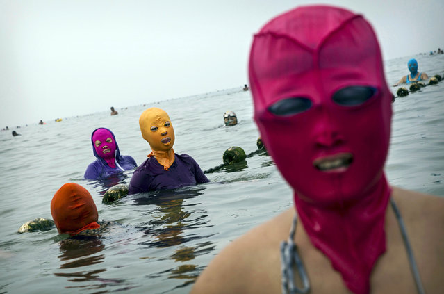 Chinese women wear face-kinis as they swim on August 21, 2014 on the Yellow Sea in Qingdao, China. The locally designed mask is worn by many local women to protect them from jellyfish stings, algae and the sun's ultraviolet rays. (Photo by Kevin Frayer/Getty Images)