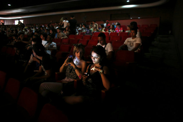 People use cell phones and tablets at a cinema where the Cuban Otaku festival is taking place in Havana, Cuba, July 24, 2016. (Photo by Alexandre Meneghini/Reuters)
