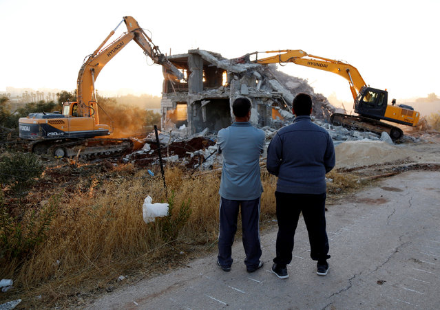 Palestinians watch as Israeli machinery demolish a Palestinian house in the West Bank village of Qalandia near Ramallah July 26, 2016. Israeli authorities demolished a dozen Palestinian homes in Qalandia, according to Palestinian sources. Witnesses added that shortly after midnight, a convoy of dozens of military vehicles and Israeli bulldozers stormed the resort, before demolishing 11 houses. (Photo by Mohamad Torokman/Reuters)