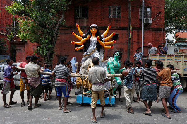 Labourers prepare to load an idol of the Hindu goddess Durga onto a truck to transport it to a pandal, or a temporary platform, for the upcoming festival of Durga Puja in Kolkata, India, September 20, 2017. (Photo by Rupak De Chowdhuri/Reuters)