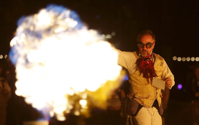 "Samuel Coniglio controls the flames by dancing at the Charcade during the Burning Man 2015 """"Carnival of Mirrors"" arts and music festival in the Black Rock Desert of Nevada, September 1, 2015. (Photo by Jim Urquhart/Reuters)"