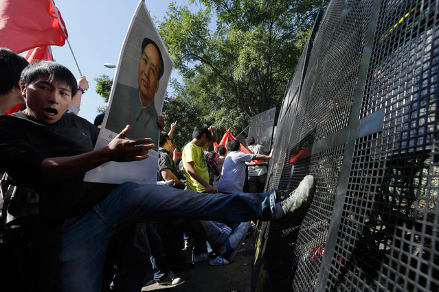 Chinese protesters kick barricades during an anti-Japan protest outside the Japanese embassy in Beijing, on September 15, 2012. (Photo by Ng Han Guan/AP Photo)
