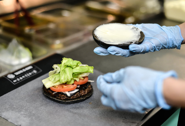 A Burger King employee prepares a black burger at a company restaurant on September 18, 2014 in Tokyo, Japan. (Photo by Keith Tsuji/Getty Images)