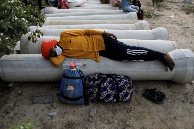 A migrant worker rests next to his belongings as he waits to cross the border to his home state of Uttar Pradesh, during an extended nationwide lockdown to slow the spread of the coronavirus disease (COVID-19), in New Delhi, India, May 16, 2020. (Photo by Adnan Abidi/Reuters)