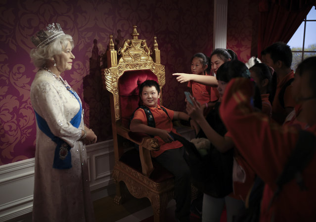 A student, center, sitting on a mock-up of the royalty chair, looks at a wax figure of Britain's Queen Elizabeth II, while others take souvenir photos, at the Madame Tussauds Museum in Beijing, China Friday, September 19, 2014.  Scottish voters have resoundingly rejected independence, deciding to remain part of the United Kingdom after a historic referendum that shook the country to its core. (Photo by Andy Wong/AP Photo)