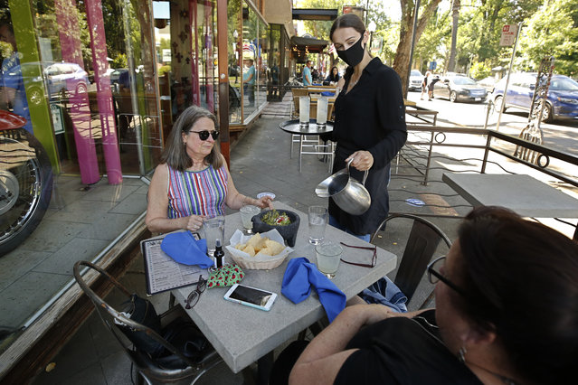 Delaney Thayer wears a face mask as she serves diners Jennifer Allen, left, and Julie Steacy at Centro Cocina Mexicana restaurant in Sacramento, Calif., Friday, May 22, 2020. As part of Sacramento County's extended Stage 2 reopening plan, dine-in restaurants and retail stores were allowed to open at noon Friday after being closed for several months due to the coronavirus pandemic. (Photo by Rich Pedroncelli/AP Photo)