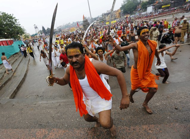 "Sadhus or Hindu holy men hold swords as they run towards the banks of Godavari river to take a dip during the second ""Shahi Snan"" (grand bath) at Kumbh Mela or Pitcher Festival in Nashik, India, September 13, 2015. (Photo by Adnan Abidi/Reuters)"