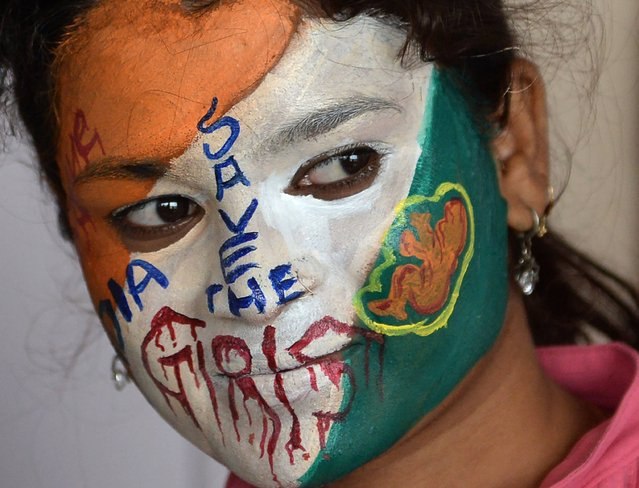 """A student with her face painted with the social message, """"save the girls"""" looks on at a college in Mumbai on August 13, 2016, ahead of Independence Day on August 15. (Photo by Indranil Mukherjee/AFP Photo)"""
