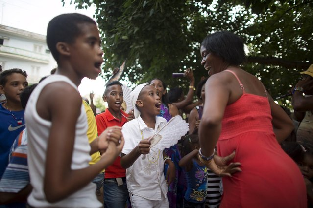 Yensy Villarreal, 9, (C), who lives in Miami, dances in the backyard of his home with friends and his mother (R) in celebration for becoming a Santero after passing a year-long rite of passage  in the Afro-Cuban religion Santeria, Havana, July 5, 2015. (Photo by Alexandre Meneghini/Reuters)