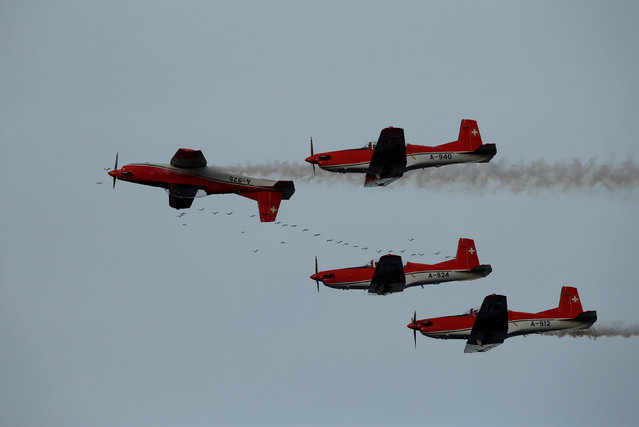 The PC-7 aerobatic team of the Swiss Air Force take part in the Malta International Airshow as a flock of birds flies by at SmartCity Malta outside Kalkara, Malta, September 23, 2017. (Photo by Darrin Zammit Lupi/Reuters)