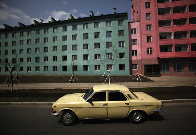 A car drives past residential buildings in Pyongyang, April 11, 2012. (Photo by Bobby Yip/Reuters)