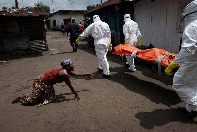 A woman crawls towards the body of her sister as Ebola burial team members take Mekie Nagbe, 28, for cremation, in Monrovia, Liberia, on October 10, 2014. Nagbe, a market vendor, collapsed and died outside her home earlier in the morning while leaving to walk to a treatment center. The burial of loved ones is important in Liberian culture, making the removal of infected bodies for cremation all the more traumatic for surviving family members. (Photo by John Moore/Getty Images)