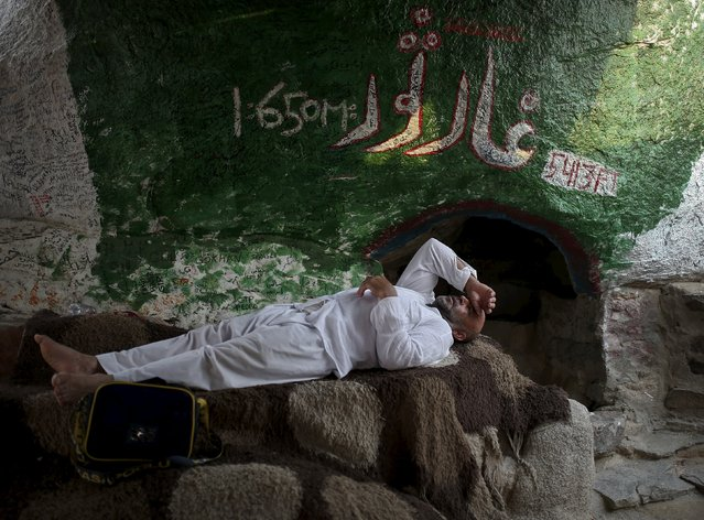 A Muslim pilgrim takes rest in front of the Thor cave at Mount Thor in the holy city of Mecca ahead of the annual haj pilgrimage September 19, 2015. (Photo by Ahmad Masood/Reuters)