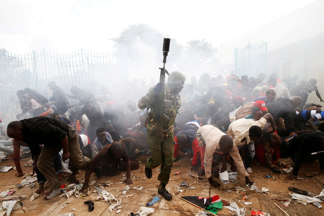 People fall as police fire tear gas to try control a crowd trying to force their way into a stadium to attend the inauguration of President Uhuru Kenyatta at Kasarani Stadium in Nairobi, Kenya, November 28, 2017. (Photo by Baz Ratner/Reuters)