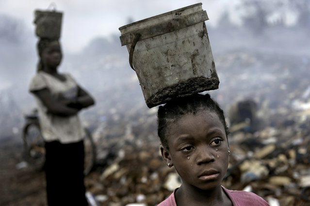 In an e-waste dump that kills nearly everything that it touches, Fati, 8, works with other children searching through hazardous waste in hopes of finding whatever she can to exchange for pennies in order to survive. While balancing a bucket on her head with the little metal she has found, tears stream down her face as the result of the pain that comes with the malaria she contracted some years ago. This is work she must do to survive. (Photo by Renée C. Byer/Living on a Dollar a Day)