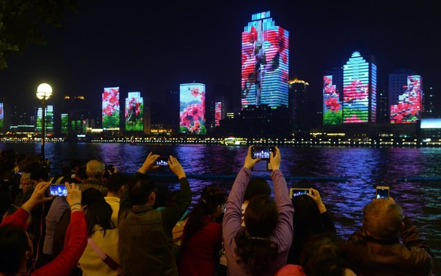 People take photos of lit buildings along the Pearl River (aka Zhujiang) on day one of 2017 Fortune Global Forum on December 6, 2017 in Guangzhou, Guangdong Province of China. The 2017 Fortune Global Forum is held on Dec 6-8 in Guangzhou. (Photo by VCG/VCG via Getty Images)