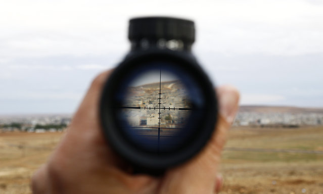 A general view of the Syrian town of Kobani is seen through a spy-glass from near the Mursitpinar border crossing, on the Turkish-Syrian border in the southeastern town of Suruc, October 19, 2014. (Photo by Kai Pfaffenbach/Reuters)