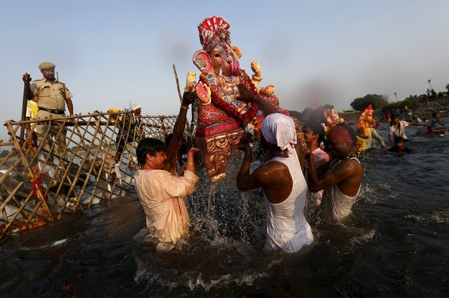 Devotees carry a statue of the Hindu god Ganesh, the deity of prosperity, to be immersed into the polluted waters of the river Yamuna on the last day of the Ganesh Chaturthi festival, in New Delhi, India, September 27, 2015. (Photo by Adnan Abidi/Reuters)