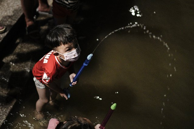 A boy wears a mask while playing in flooded waters at Jiangtan Park caused by heavy rains along the Yangtze river on July 9, 2020 in Wuhan, China. On July 5, Wuhan upgraded its emergency response for flood control from Grade III to Grade II, the second-highest of the four-tier system following weeks of torrential rain which have reportedly left at least 121 dead or missing. (Photo by Getty Images)