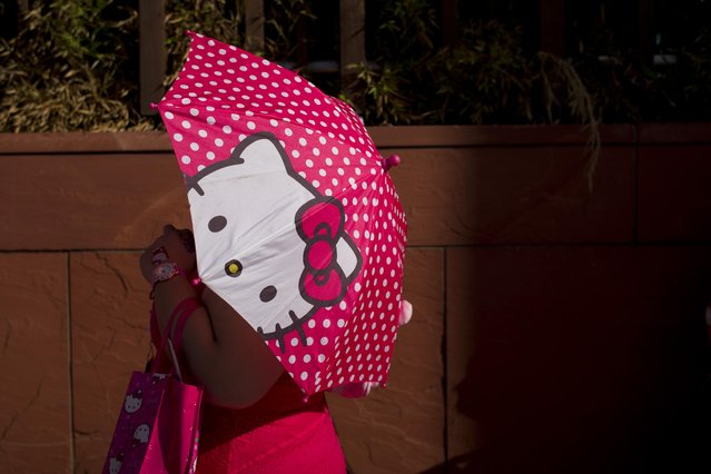 A woman uses a Hello Kitty umbrella to shelter from the sun while waiting in line for the Hello Kitty Con, the first-ever Hello Kitty fan convention, held at the Geffen Contemporary at MOCA Thursday, October 30, 2014, in Los Angeles. (Photo by Jae C. Hong/AP Photo)