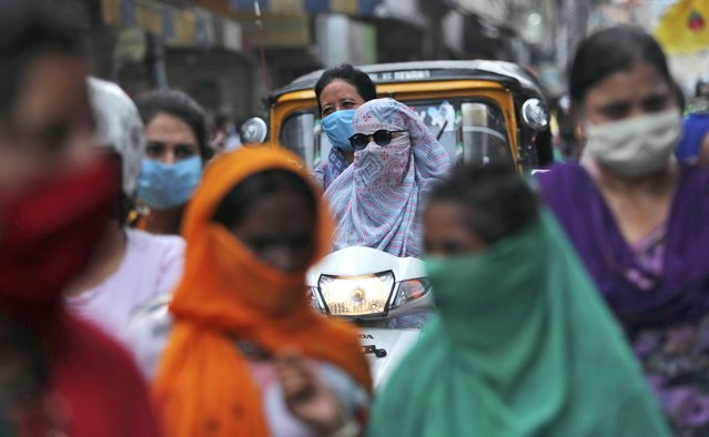 Indians wearing face masks as a precaution against the coronavirus walk at a market in Jammu, India, Monday, August 10, 2020. (Photo by Channi Anand/AP Photo)