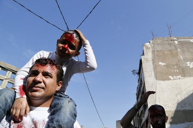 A Shi'ite Muslim boy and his guardian are covered with blood after cutting their heads with a razor during the Ashoura ceremony held in Beirut November 4, 2014. (Photo by Jamal Saidi/Reuters)