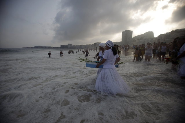 Followers of Afro-Brazilian religion Umbanda carry flowers and offerings for Iemanja, goddess of the sea, in Copacabana Beach in Rio de Janeiro December 29, 2012. Every end of the year, worshippers present gifts to the sea goddess to give thanks for the year that is finishing and ask for blessings for the upcoming new year. (Photo by Ricardo Moraes/Reuters)