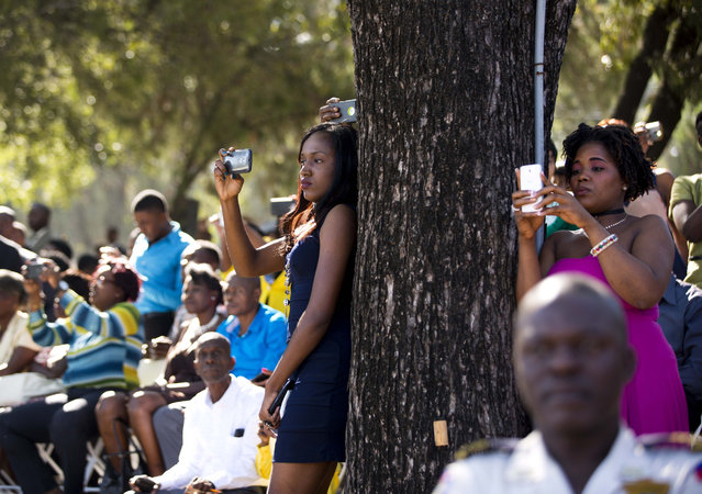 Relatives and friends take pictures of national police officers during their graduation ceremony in Port-au-Prince, Haiti, on December 18, 2017. (Photo by Dieu Nalio Chery/AP Photo)