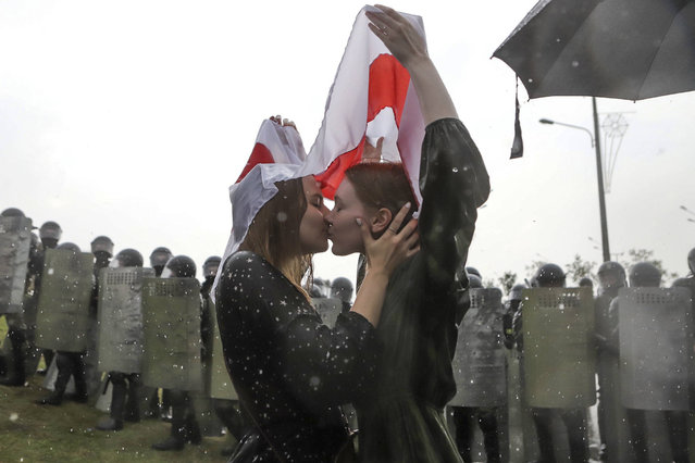 Two women kiss covered by an old Belarusian national flag as Belarusian opposition supporters gather towards the Independence Palace in Minsk, Belarus, Sunday, August 30, 2020. Tens of thousands of demonstrators have gathered in the capital of Belarus, beginning the fourth week of daily protests demanding that the country's authoritarian president resign. The protests began after an Aug. 9 presidential election that protesters say was rigged and officials say gave President Alexander Lukashenko a sixth term in office. (Photo by AP Photo/Stringer)