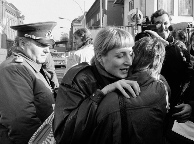 An East Berlin citizen (C) embraces a West Berlin woman while an East German border soldier watches on at the border checkpoint Invalidenstrasse after the opening of the East German border was announced in Berlin, November 9, 1989. (Photo by Fabrizio Bensch/Reuters)
