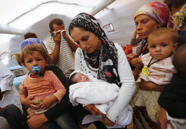 Kurdish Syrian refugees are seen with children inside a temporary medical facility for children on the Turkish-Syrian border near the southeastern town of Suruc in Sanliurfa province, in this September 24, 2014 file photo. (Photo by Murad Sezer/Reuters)